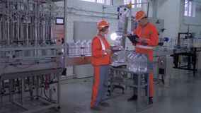 Factory workers man and female into helmet and overall near conveyor line for bottling mineral water in plastic bottles stock video