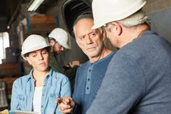 Factory workers in a meeting. Planning in teamwork royalty free stock image
