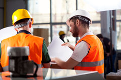Factory workers planning. Male factory worker and supervisor are analyzing plans royalty free stock photo