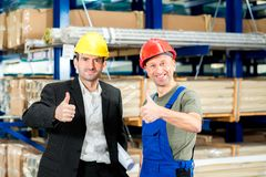 Boss and worker with thumb up. In the factory- young boss and worker with thumb up royalty free stock photos