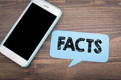 Facts concept. Speech Bubble on a dark textured wooden background Royalty Free Stock Photo