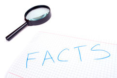 Facts and hand magnifier Stock Images