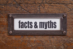 Facts and myths. File cabinet label, bronze holder against grunge and scratched wood Stock Photography