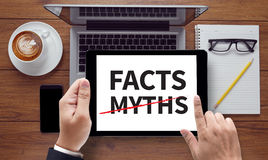 FACTS  -MYTHS. On the tablet pc screen held by businessman hands - online, top view Stock Photo