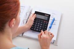 Factura calculadora de la mujer en el escritorio Imágenes de archivo libres de regalías