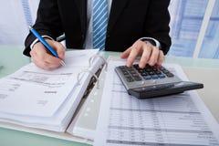 Factura calculadora del hombre de negocios en el escritorio de oficina Imagen de archivo