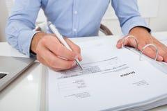 Factura calculadora del hombre de negocios en oficina Fotos de archivo libres de regalías
