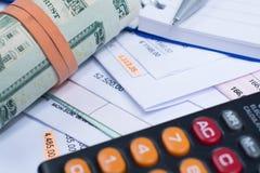 Facturas y cuentas, rollo de los billetes de banco del dólar, calculadora, closeu Fotografía de archivo