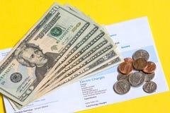Facture de charges électriques avec l'argent liquide sur le jaune photos stock