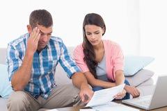 Facture de lecture de couples tandis que finances calculatrices de maison Image libre de droits