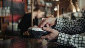 Facture de paiement d'homme par le smartphone utilisant la technologie de NFC en limonade de boissons de café à aller clips vidéos