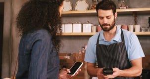 Facture de paiement de femme par le smartphone utilisant la technologie de nfc banque de vidéos