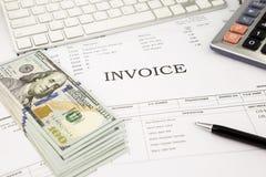 Facture los documentos y los billetes de banco del dinero del dólar en la tabla de la oficina Imagen de archivo