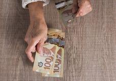 Factures d'argent liquide de devise canadienne Dollars Au-dessus de la vue de la personne retrait?e ?g?e payant comptant photographie stock libre de droits