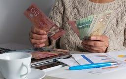 Factures d'argent liquide de devise canadienne Dollars Dame ?g?e comptant des factures sur la table photographie stock