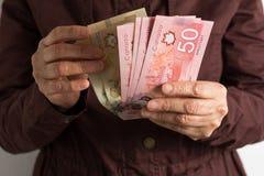 Factures d'argent liquide de devise canadienne Dollars Personne retrait?e ?g?e payant comptant photos libres de droits