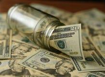 Factures de dollar US dans le pot en verre avec d'autres dollars autour au foyer mou Photographie stock