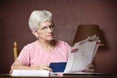Factures de paiement aînées de femme Photos stock