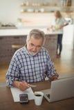 Factures de paiement d'homme supérieur en ligne sur l'ordinateur portable dans la cuisine Photos libres de droits