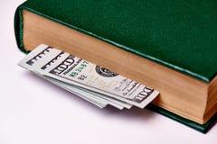 Factures en valeur cent dollars US dans le livre sur un macro blanc de fond photographie stock libre de droits