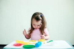 Faculdade criadora das crianças A criança esculpe da argila 2 anos pequenos bonitos dos moldes da menina do plasticine na tabela  foto de stock royalty free