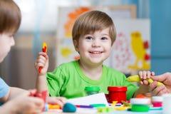 Faculdade criadora das crianças Crianças que esculpem da argila Os rapazes pequenos bonitos moldam do plasticine na tabela no jar Fotografia de Stock Royalty Free