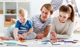 Faculdade criadora do ` s das crianças tração feliz do pai e do filho da mãe da família imagens de stock