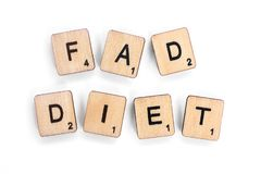 FAD DIET. London, UK - July 8th 2018: The phrase FAD DIET - spelt with wooden letter tiles over a white background royalty free stock photos