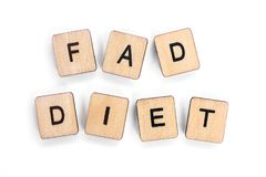 FAD DIET. The phrase FAD DIET - spelt with wooden letter tiles over a white background royalty free stock photography