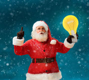 Faddish Santa Claus with open mouth and finger pointing up, showing light bulb banner. Santa Claus on blue background having a good idea. Happy New Year Royalty Free Stock Image
