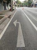 Faded biegen Zeichen auf Straße nach links ab stockbild