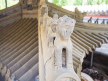 Faded blue clay mythical roof figurines and eaves stock image