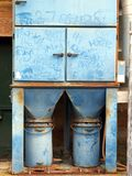 Industrial Waste Hopper and Bins. A faded blue metal industrial waste or rubbish hopper, with two rubbish or trash bins. Ad hoc graffiti scratched in paint stock photography