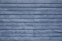 Faded blue siding. Old, weathered, faded blue, chipped paint on wood siding wall stock photo