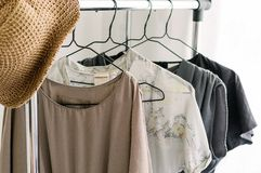 Faded colors dresses on wardrobe rail. Straw hat fedora. Summer outfits. Faded colors dresses on wardrobe rail. Blush pink, grey fashion dresses, summer style stock images