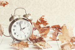 Faded Daylight Savings Time. Faded Alarm clock in colorful autumn leaves against a retro background with shallow depth of field. Daylight savings time concept stock photos