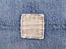 Faded Denim Pocket. Close up of a faded blue jeans pocket with a blank, frayed tan denim tag Royalty Free Stock Photography