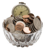 Faded old pocket watch coins time money concept. An inexpensive antique faded pocket watch and crystal glass bowl of American pocket coins shows the time money Royalty Free Stock Photography