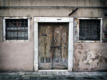 Faded old run down empty house in venice with cracked walls and bolted peeling wooden door with bars on the windows. A faded old run down empty house in venice royalty free stock image