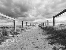 A path made of sand which has fences on both sides Royalty Free Stock Photo
