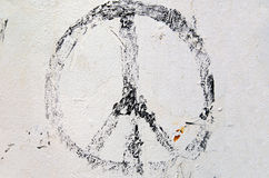 Faded peace sign. Worn peace sign on white painted wall royalty free stock photography