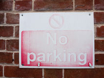 A faded red and white retro vintage no parking sign with texture stock images