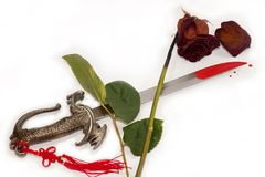 Faded rose, blood-stained knife, means the end of Stock Photo