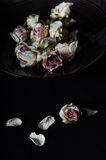 Faded roses in bowl. And single rose and petals on black table Stock Photo