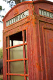 Faded and rusty British telephone booth. This old telephone booth is a remnant of retro communications with paint peeling in layers Royalty Free Stock Image