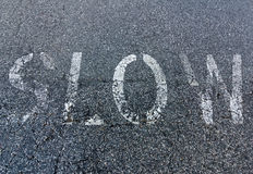 Faded Slow Sign Painted on Asphalt Royalty Free Stock Photo
