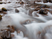 Faded stream. Streaming water in a river is faded by long exposure Stock Photo
