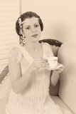 Faded vintage tea party. Attractive vintage 1920s woman sitting on a chaise longue stock photography