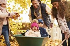 Fader In Autumn Garden Gives Children Ride i skottkärra royaltyfria bilder
