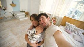 Fader av den lyckliga familjen som tar selfievideoen på kamera i sovrum arkivfilmer
